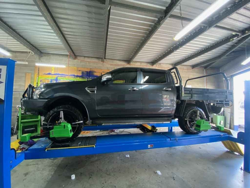 Picture Of A Black Car Receiving A Wheel Alignment Service